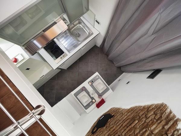 Thiết kế phòng bếp nhỏ xinh tiện nghe với đầy đủ hút mùi, bếp ga, giá để bát, thậm chí cả bàn ăn gập lại được