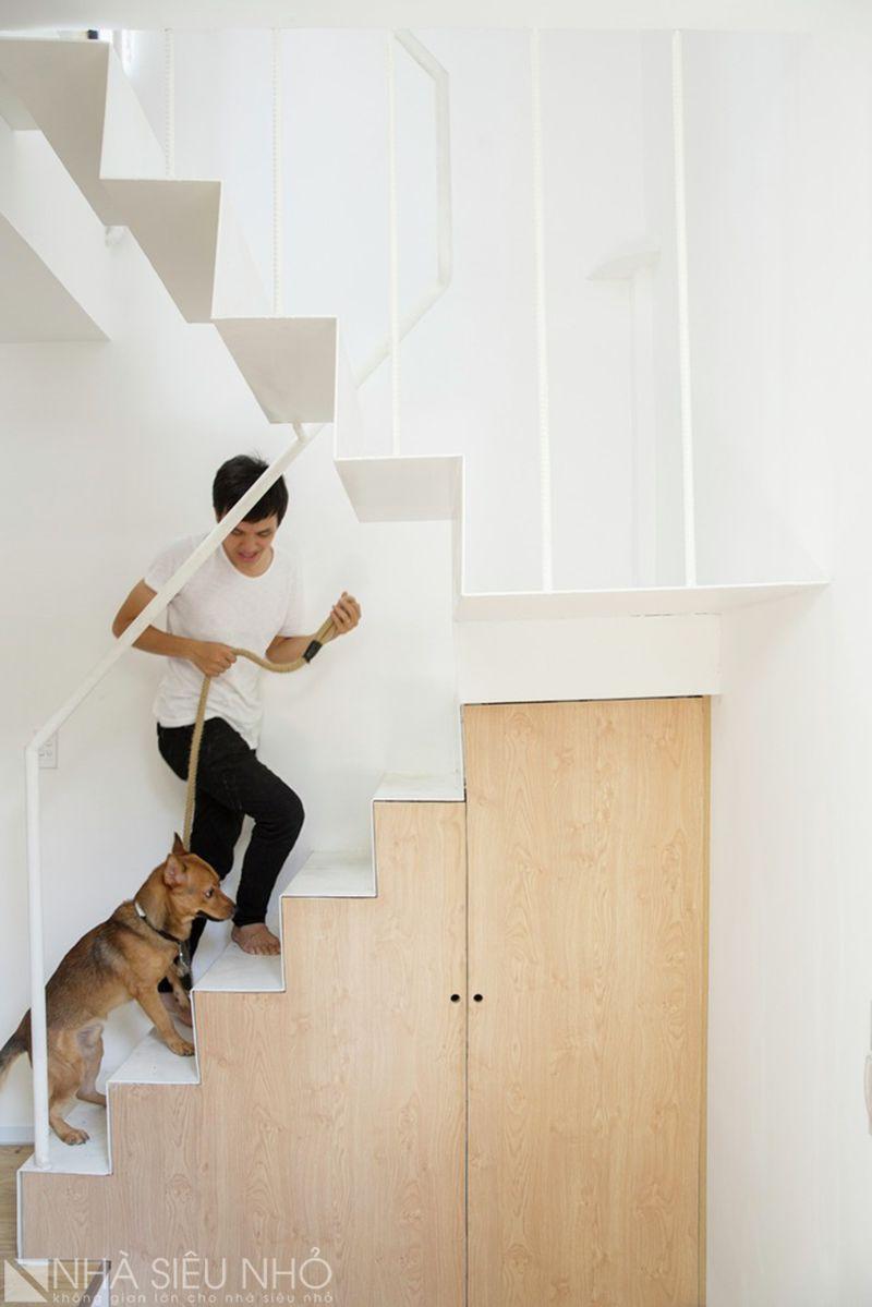 Cầu thang thép sơn trắng, dưới gầm thang là tủ đựng đồ